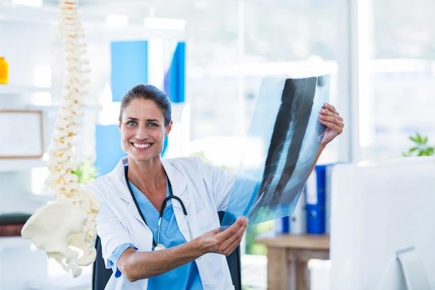 Lächelnder doktor, der röntgenstrahlen betrachtet