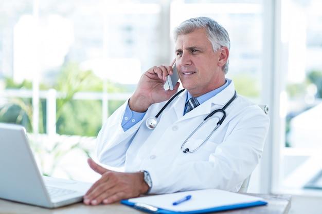 Lächelnder doktor, der telefonanruf an seinem schreibtisch hat