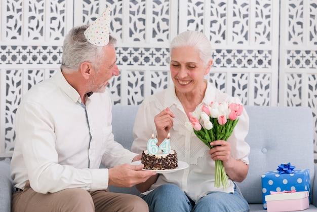 Lächelnder ehemann, der seiner frau tragenden partyhut geburtstagskuchen gibt