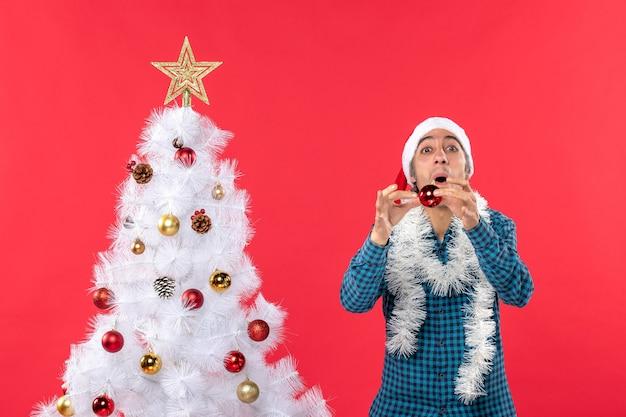 Lächelnder emotionaler lustiger aufgeregter junger mann mit weihnachtsmannhut in einem blauen gestreiften hemd