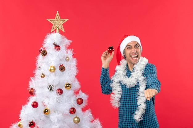 Lächelnder emotionaler lustiger aufgeregter selbstbewusster junger mann mit weihnachtsmannhut in einem blauen gestreiften hemd