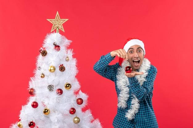 Lächelnder emotionaler lustiger junger mann mit weihnachtsmannhut in einem blauen gestreiften hemd und im halten des dekorationszubehörs, das nahe weihnachtsbaum auf rot steht