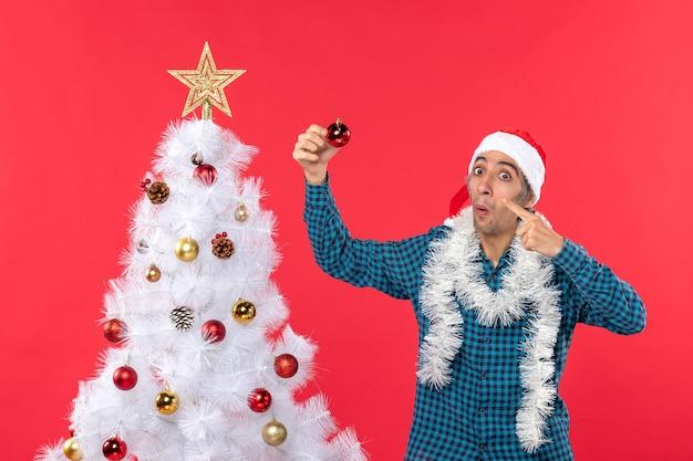 Lächelnder emotionaler lustiger junger mann mit weihnachtsmannhut in einem blauen gestreiften hemd