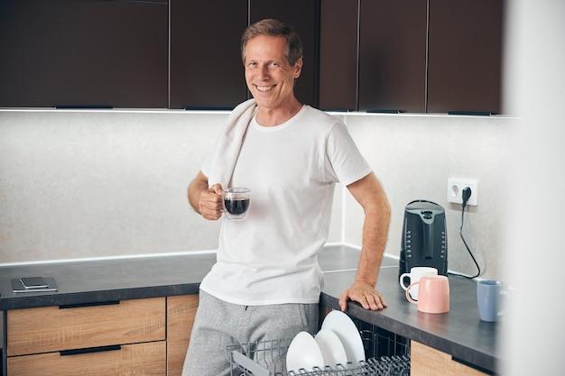 Lächelnder entspannter erwachsener mann, der in der küche steht und seinen aromakaffee genießt enjoying