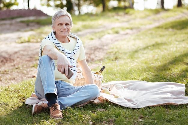 Lächelnder entzückter gutaussehender mann, der glück ausdrückt, während er wetter im park genießt und picknick hat