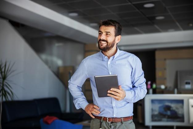 Lächelnder erfolgreicher bärtiger chef, der in der lobby der reederei steht, tablette hält und hand auf hüfte hält.