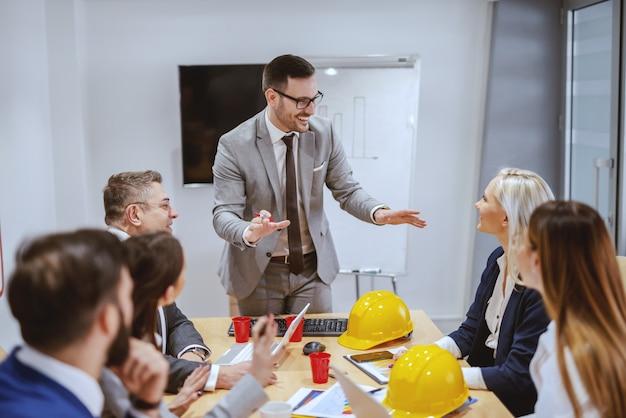 Lächelnder erfolgreicher geschäftsmann, der steht und über neues projekt spricht, während sein team im sitzungssaal sitzt und fragen stellt. wenn sie größe erreichen wollen, hören sie auf, um erlaubnis zu bitten.
