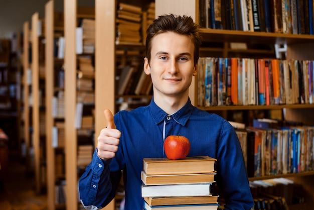 Lächelnder erfolgreicher junger student, der daumen oben in bibliothek zeigt