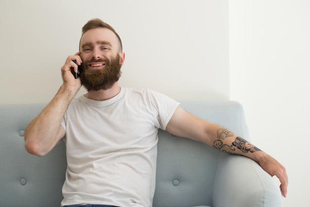 Lächelnder erfüllter junger mann mit bart unter verwendung des handys