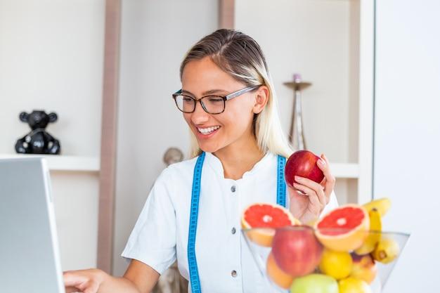 Lächelnder ernährungswissenschaftler im büro, das eine frucht hält