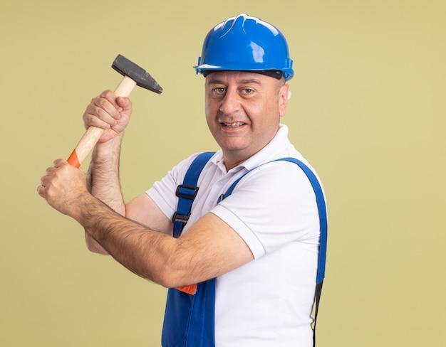 Lächelnder erwachsener baumeister in uniform hält hammer auf olivgrün