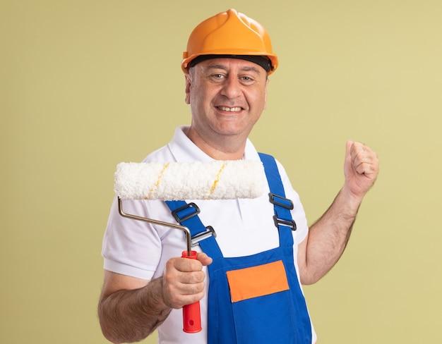 Lächelnder erwachsener baumeistermann in der uniform hält rollbürste und zeigt zurück lokalisiert auf olivgrüner wand