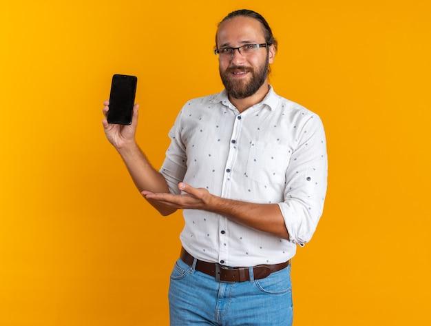 Lächelnder erwachsener gutaussehender mann mit brille, der die kamera anschaut und das mobiltelefon zeigt, das auf eine orangefarbene wand zeigt?