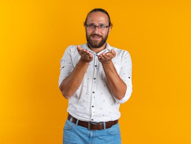 Lächelnder erwachsener gutaussehender mann mit brille, der die kamera anschaut und leere hände zeigt, die auf orangefarbener wand mit kopierraum isoliert sind?