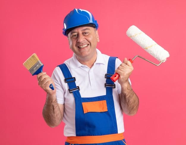 Lächelnder erwachsener kaukasischer baumeistermann in der uniform hält pinsel und walzenpinsel auf rosa