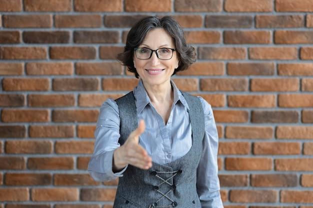 Lächelnder erwachsener kaukasischer geschäftsfrauenführer mit brille dehnen sich die hand, die neuen mitarbeiter am arbeitsplatz im büro grüßt. rekrutierungskonzept