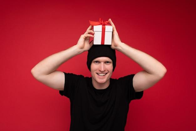 Lächelnder erwachsener mann lokalisiert auf der roten hintergrundwand, die schwarzen hut und schwarzes t-shirt hält, die weiße geschenkbox mit rotem band hält und kamera betrachtet und spaß hat.