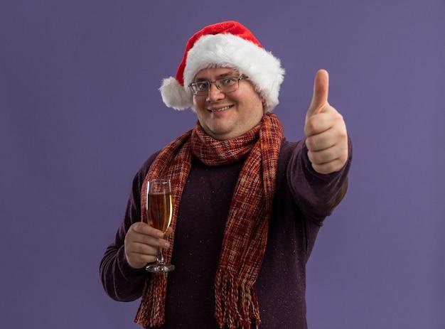 Lächelnder erwachsener mann mit brille und weihnachtsmütze mit schal um den hals, der ein glas champagner hält, der daumen nach oben isoliert auf lila wand zeigt