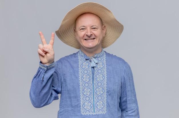 Lächelnder erwachsener mann mit strohhut und im blauen hemd, der siegeszeichen gestikuliert