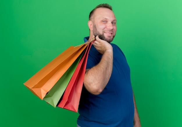 Lächelnder erwachsener slawischer mann, der einkaufstaschen auf schulter hält, die lokal schaut