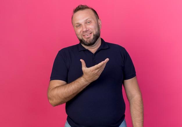 Lächelnder erwachsener slawischer mann, der leere hand zeigt, die isoliert schaut