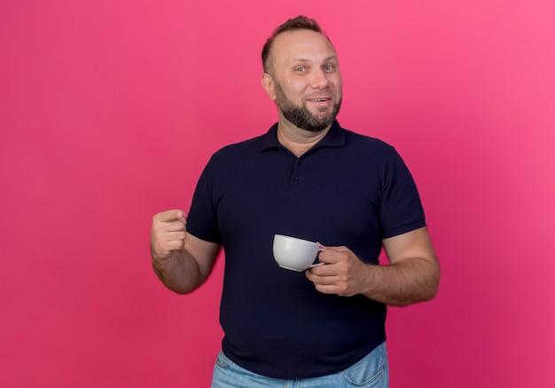 Lächelnder erwachsener slawischer mann, der tasse hält und lokal zeigt