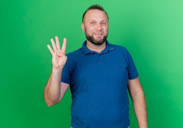 Lächelnder erwachsener slawischer mann, der vier mit der hand lokalisiert auf grüner wand mit kopienraum zeigt