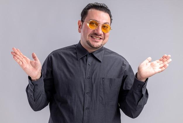 Lächelnder erwachsener slawischer mann mit sonnenbrille, der die hände offen hält