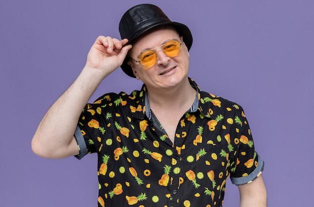 Lächelnder erwachsener slawischer mann mit sonnenbrille, der seinen zylinder hält und nach vorne schaut