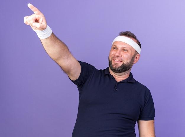 Lächelnder erwachsener slawischer sportlicher mann, der stirnband und armbänder trägt, die lokal auf lila wand mit kopienraum suchen und zeigen
