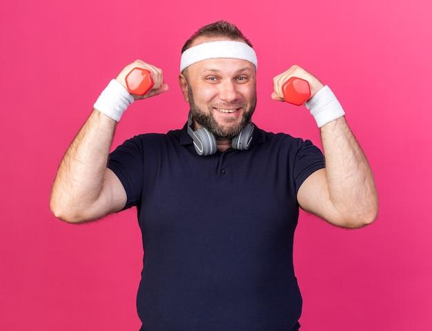 Lächelnder erwachsener slawischer sportlicher mann mit kopfhörern, die stirnband und armbänder tragen, die hanteln lokalisiert auf rosa wand mit kopienraum halten