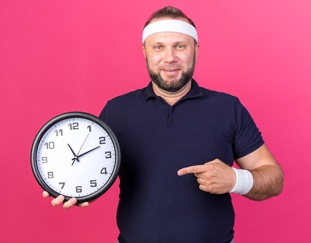 Lächelnder erwachsener slawischer sportlicher mann mit stirnband und armbändern, der die uhr isoliert auf rosa wand mit kopierraum hält und zeigt