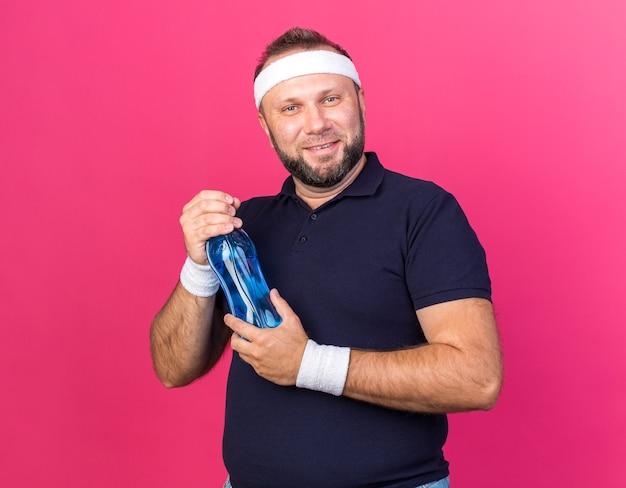 Lächelnder erwachsener slawischer sportlicher mann mit stirnband und armbändern, der eine wasserflasche isoliert auf rosa wand mit kopienraum hält