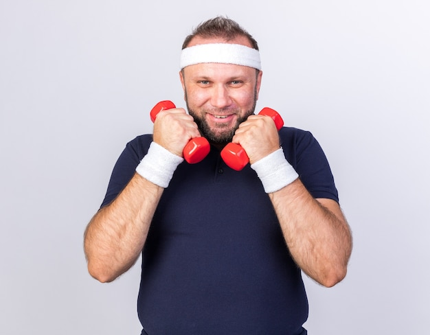 Lächelnder erwachsener slawischer sportlicher mann mit stirnband und armbändern, der hanteln isoliert auf weißer wand mit kopienraum hält
