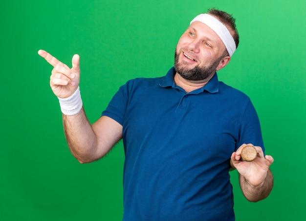Lächelnder erwachsener slawischer sportlicher mann mit stirnband und armbändern, der schläger hält und auf die seite zeigt, isoliert auf grüner wand mit kopierraum
