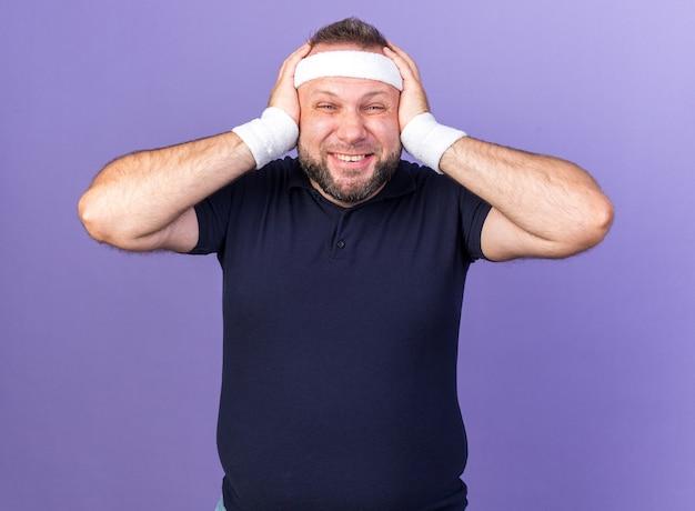 Lächelnder erwachsener slawischer sportlicher mann mit stirnband und armbändern, der seinen kopf isoliert auf lila wand mit kopienraum hält