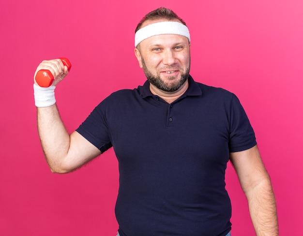 Lächelnder erwachsener slawischer sportlicher mann mit stirnband und armbändern mit hantel isoliert auf rosa wand mit kopierraum