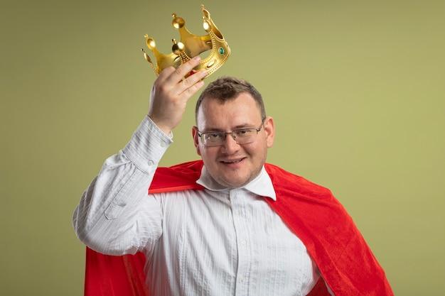 Lächelnder erwachsener slawischer superheldenmann im roten umhang, der brille hält krone über kopf lokalisiert auf olivgrüner wand trägt