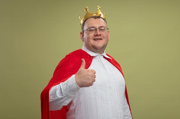 Lächelnder erwachsener slawischer superheldenmann in der roten umhang tragenden brille und in der krone, die kamera zeigt, zeigt daumen oben lokalisiert auf olivgrünem hintergrund mit kopienraum