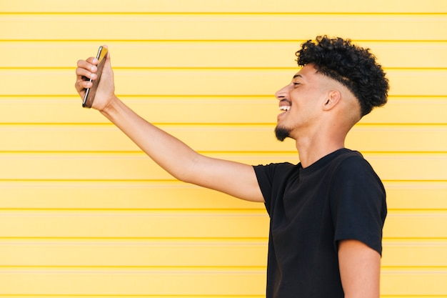 Lächelnder ethnischer mann, der selfie nimmt