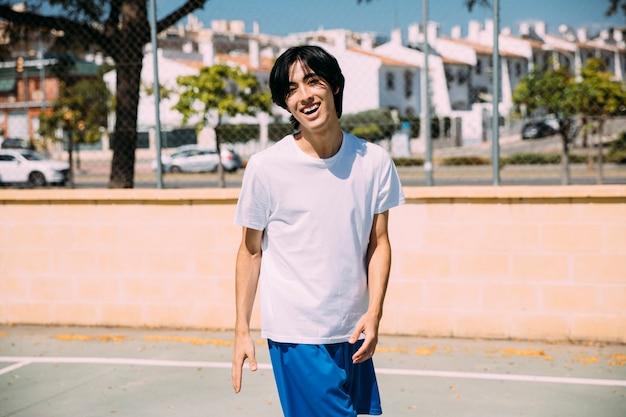 Lächelnder ethnischer mann in der sportkleidung, die auf spielplatz steht