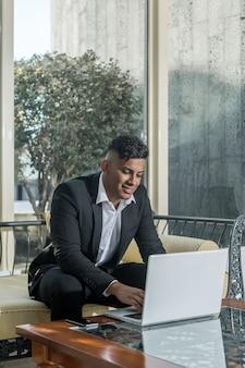 Lächelnder ethnischer unternehmer, der laptop verwendet