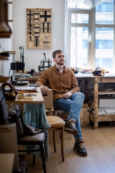 Lächelnder europäischer männlicher besitzer eines kleinunternehmens, das bei einem professionellen gerber in der lederwerkstatt posiert