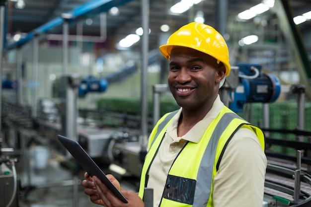 Lächelnder fabrikarbeiter, der digitales tablett in der fabrik verwendet