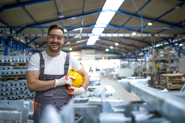 Lächelnder fabrikarbeiter mit schutzhelm, der in der fabrikproduktionslinie steht