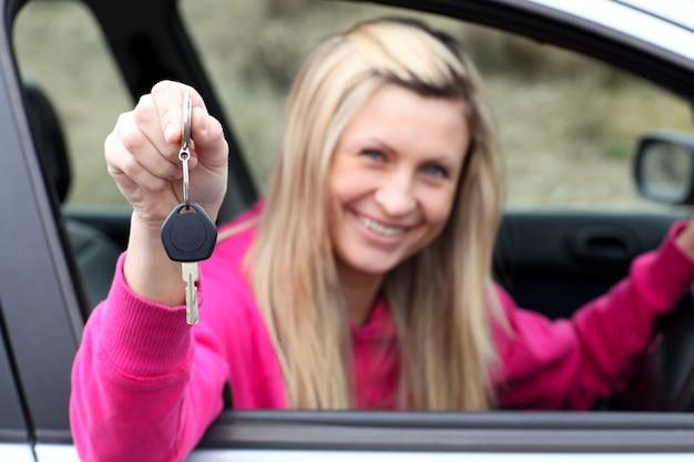 Lächelnder fahrer, der einen schlüssel zeigt, nachdem er ein neues auto bying gemacht hat