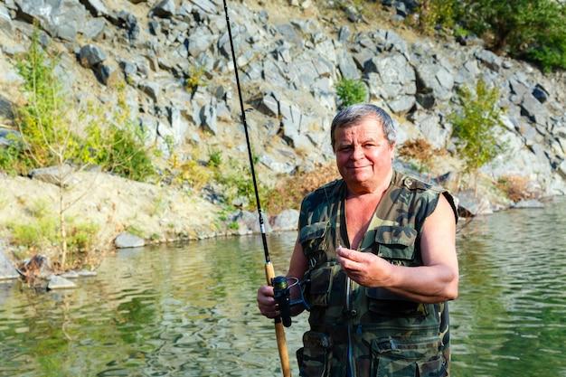 Lächelnder fischer mit einer angelrute auf einem gebirgssee
