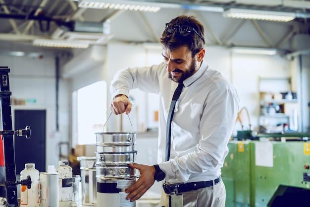 Lächelnder fleißiger kaukasischer bärtiger direktor in hemd und krawatte, die dose mit farben nimmt und mitarbeitern hilft, während sie in der druckerei stehen.