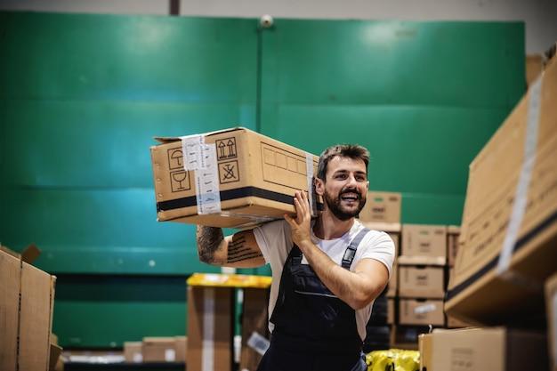 Lächelnder fleißiger tätowierter bärtiger arbeiter in overalls, der eine schachtel auf seiner schulter trägt