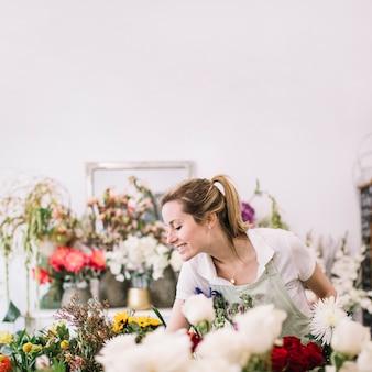 Lächelnder florist, der um blumen sich kümmert